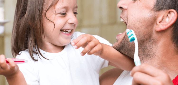 Padre e hija divirtiéndose mientras se cepillan los dientes