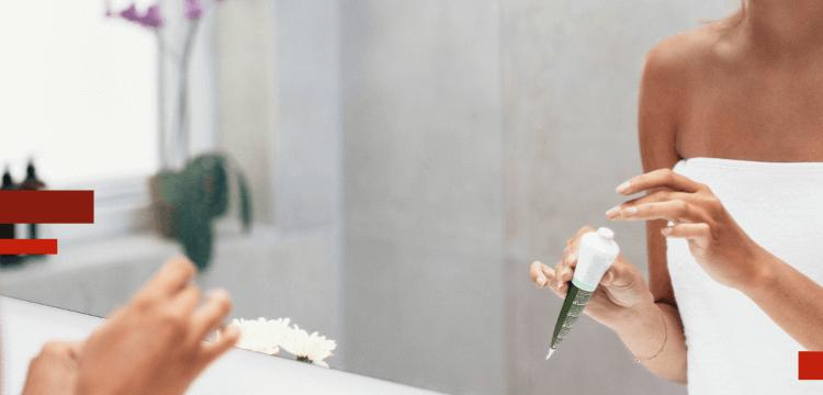 Mujer joven frente al espejo del baño usando una crema para controlar la piel grasa