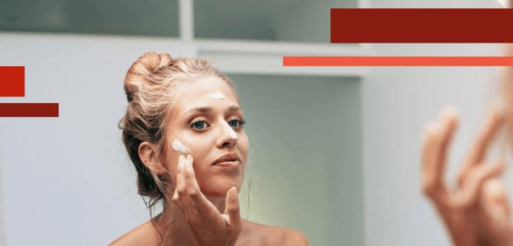 Mujer hidratándose la piel seca frente al espejo de un baño