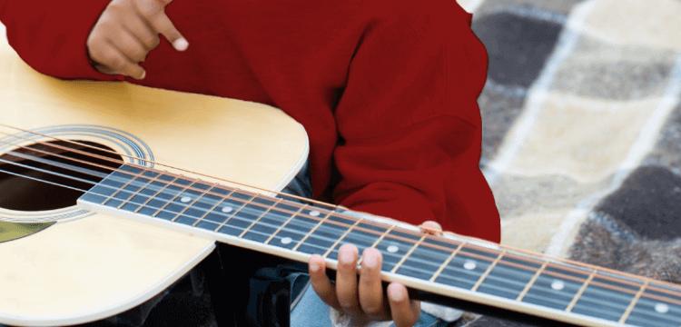 Niño pequeño tocando la guitarra sobre una alfombra de pícnic en el parque