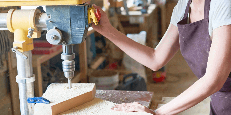 Woman with safety glasses woodworking in work studio.jpg