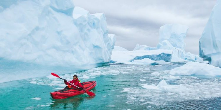 man paddling on kayak between ice.jpg