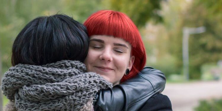 Two girls hugging each other at park.jpg