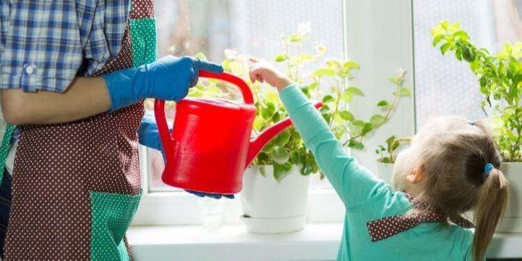 Madre e hija regando unas flores.jpg