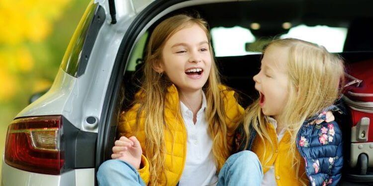 Two girls sitting in a car trunk before going on vacations.jpg
