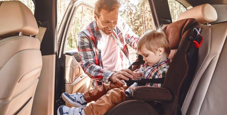 Father is adjusting child's car seat, while kid is playing with toy binoculars. Side view